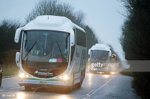 Buses carry 51 Syrian refugees to an undisclosed temporary housing location after their arrival at Belfast International Airport on December 15 2015...