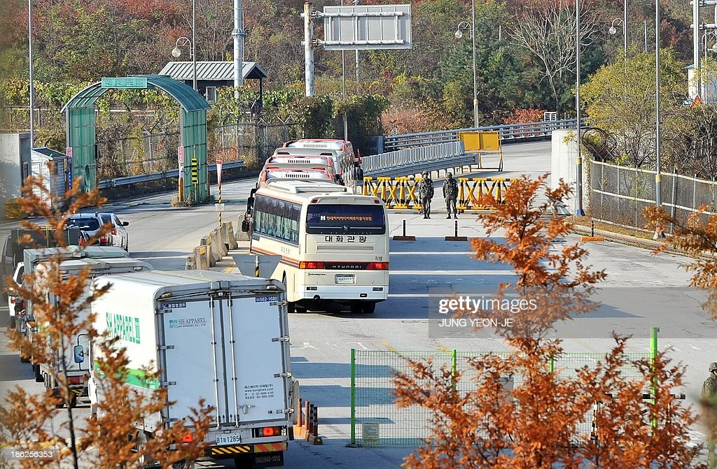 Buses (C) carrying South Korean lawmakers pass a military checkpoint as they leave for North Korea at the inter-Korean transit office in Paju near the Demilitarized zone dividing the two Koreas on October 30, 2013. A group of South Korean lawmakers crossed the border into North Korea to visit an inter-Korean factory complex in the communist country that has recently resumed operations after a five-month hiatus.