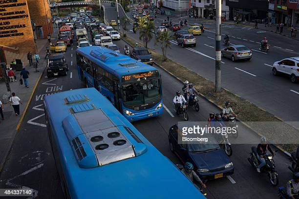 Buses from the Masivo Integrado de Occidente public transportation system travel down a street in Cali Colombia on Wednesday Aug 12 2015 Colombia's...