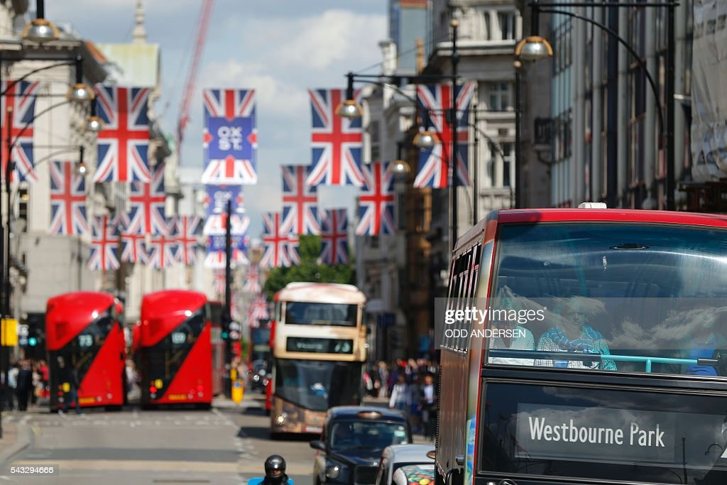 Buses travel along Oxford Street underneath Union flags in central london on June 27, 2016. Shares in banks, airlines and property companies plunged on the London stock exchange Monday as investors singled out the three sectors as being the most vulnerable to Britain's decision to leave the EU. / AFP / ODD