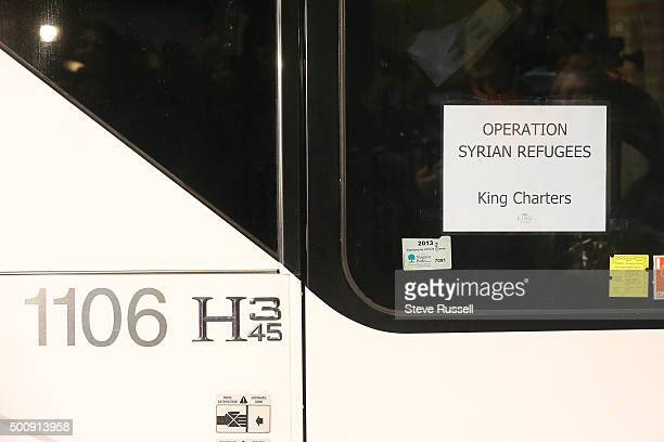 Buses with Syrian refugees arrive at an airport hotel and begin to disembark Syrian refugees begin to arrive in Canada at a hotel near Pearson...