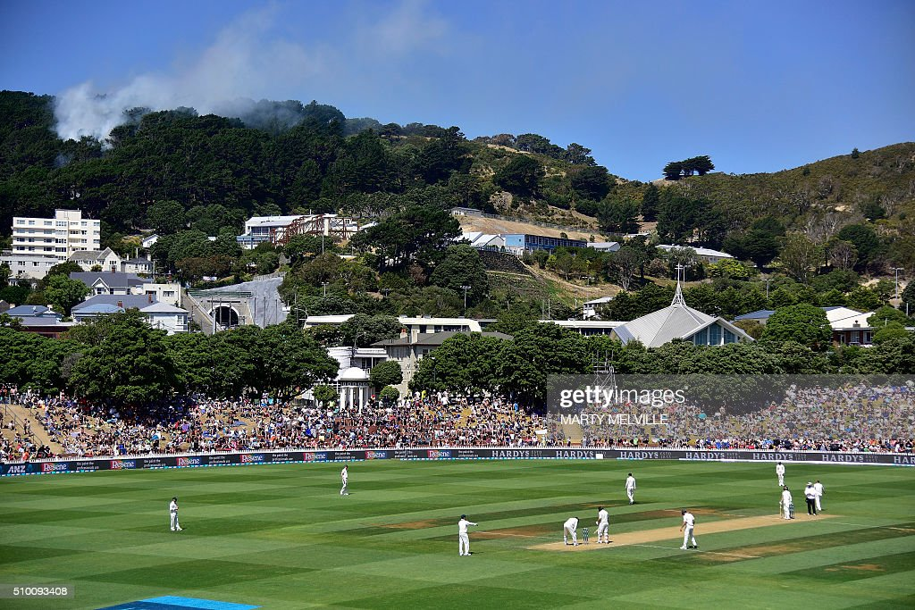 A bush fire (top-L) is seen on the hill above the Basin Reserve during day three of the first cricket Test match between New Zealand and Australia at the Basin Reserve in Wellington on February 14, 2016. AFP PHOTO / MARTY MELVILLE / AFP / Marty Melville