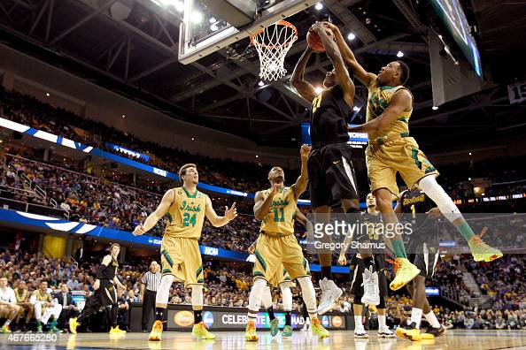Bush Wamukota of the Wichita State Shockers drives to the basket and is blocked by Bonzie Colson of the Notre Dame Fighting Irish in the first half...