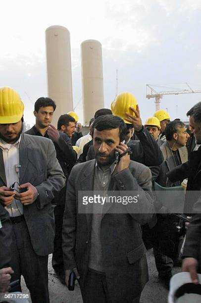Iranian President Mahmoud Ahmadinejad talks on his mobile phone during a tour of the Bushehr nuclear power plant 01 February 2006 Iran's hardline...