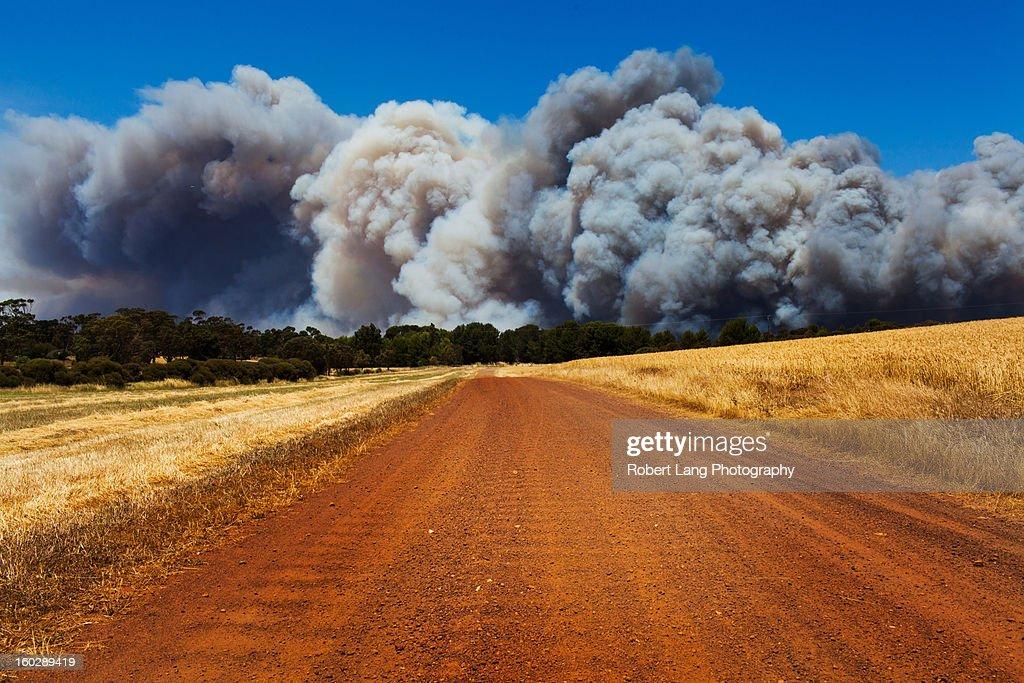 Bushfire smoke over dirt road, rural Australia : Stock Photo