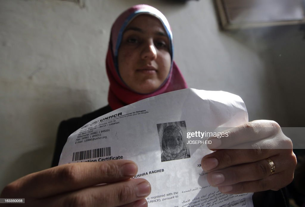 Bushra, who is the 1000000 registered Syrian refugee at the UNHCR, displays her certificate as she sits inside a shanty rented by her missing husband's family in a poor neighbourhood at the entrance of the northern Lebanese city of Tripoli on March 7, 2013. The number of Syrians who have fled their country since a deadly civil conflict erupted two years ago has hit one million, the UN's refugee agency said on March 6.
