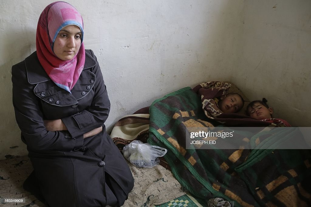 Bushra (L), who is the 1000000 registered Syrian refugee at the UNHCR, sits near her children sleeping inside a shanty rented by her missing husband's family in a poor neighbourhood at the entrance of the northern Lebanese city of Tripoli on March 7, 2013. The number of Syrians who have fled their country since a deadly civil conflict erupted two years ago has hit one million, the UN's refugee agency said on March 6.
