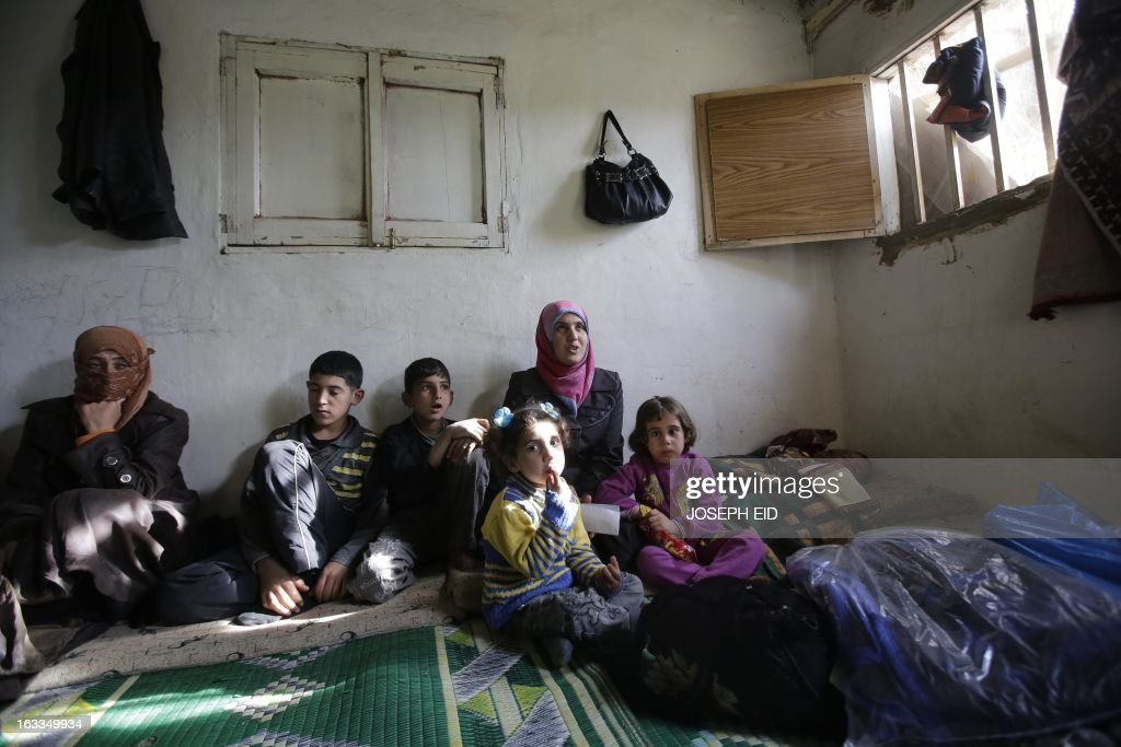 Bushra (C-top), who is the 1000000 registered Syrian refugee at the UNHCR, sits among children inside a shanty rented by her missing husband's family in a poor neighbourhood at the entrance of the northern Lebanese city of Tripoli on March 7, 2013. The number of Syrians who have fled their country since a deadly civil conflict erupted two years ago has hit one million, the UN's refugee agency said on March 6. AFP PHOTO/JOSEPH EID