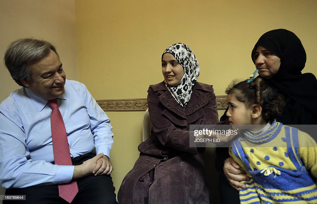 Bushra (C), who is the 1000000 registered Syrian refugee at the UNHCR shows the UN High Commissioner for Refugee's Antonio Guterres (L) her daughter as they meet at a community center in the Al-Mina neighbourhood of the northern Lebanese city of Tripoli on March 15, 2013. Guterres said the number of Syrian refugees could double or triple by the end of the year if no solution is found to the conflict.
