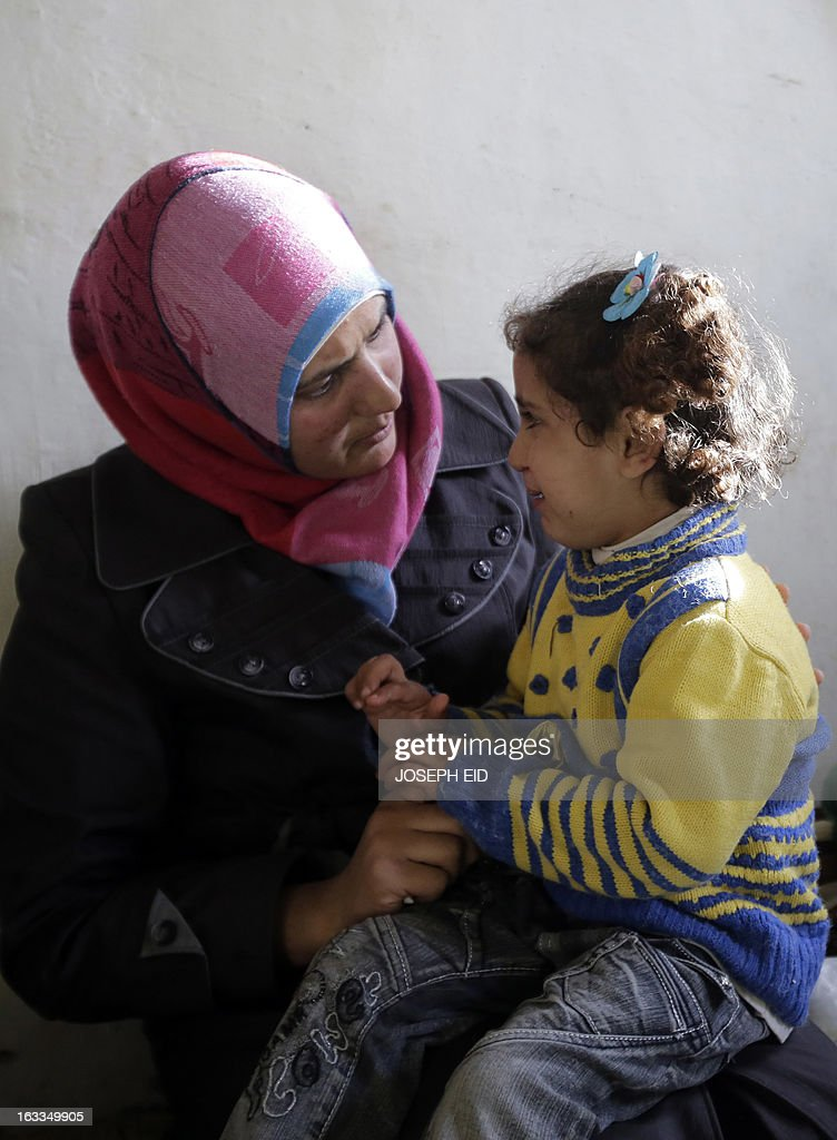 Bushra (L), who is the 1000000 registered Syrian refugee at the UNHCR, talks to her daughter inside a shanty rented by her missing husband's family in a poor neighbourhood at the entrance of the northern Lebanese city of Tripoli on March 7, 2013. The number of Syrians who have fled their country since a deadly civil conflict erupted two years ago has hit one million, the UN's refugee agency said on March 6.