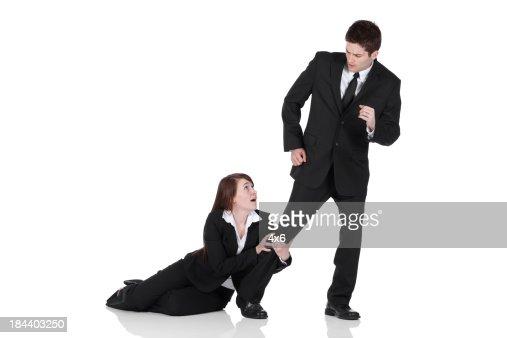 Busiesswoman holding the leg of a businessman