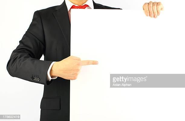 Businesman apuntando a un cartel en blanco