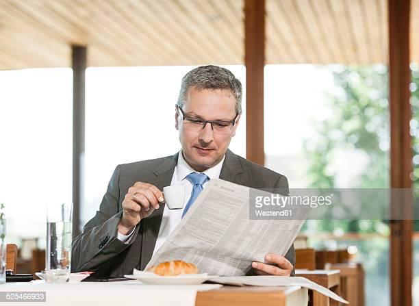 Businesman reading newspaper in restaurant