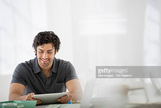 Business. A light airy office environment. A man sitting holding a digital tablet.