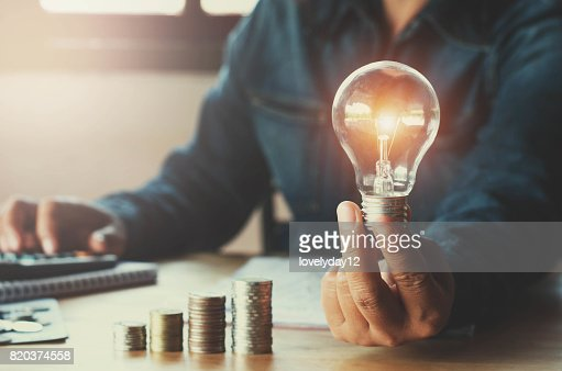 business accountin with saving money with hand holding lightbulb concept financial background : Stock Photo