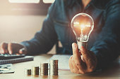 business accountin with saving money with hand holding lightbulb concept financial background