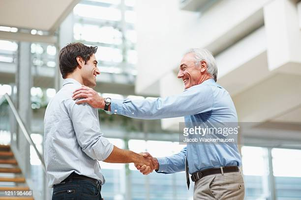 Business agreement - Senior and young executives shaking hands