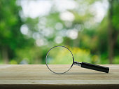 Magnifying glass on wooden table over blur tree in park, Business analyzing concept