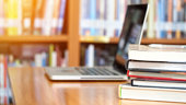 Book stack and laptop on workplace in library room with blurred focus for background, education concept