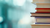 Book stack in the library room and blurred bookshelf, business and education background