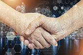 Business and technology concept. Double exposure of handshake with connection technology icons in city background.