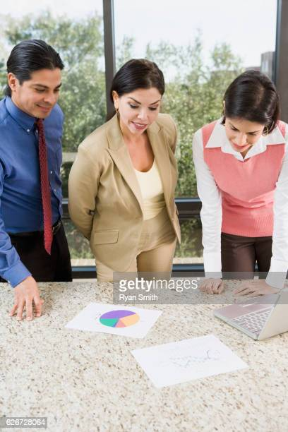 Business associates looking at a pie chart