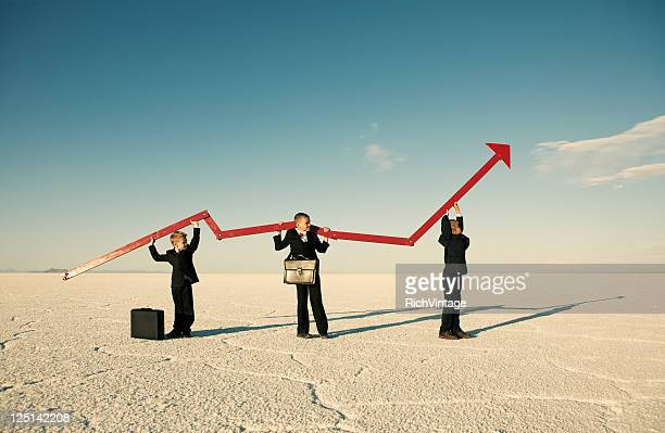 Business Boys Holding Line Graph in Desert