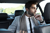 Businessman in car, looking away