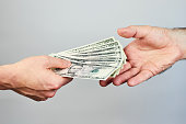 Business closeup of two hands exchanging dollars on grey background.