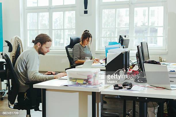 Business colleague working at computer desk in creative office