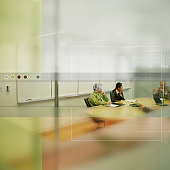 Business colleagues at table in conference room, digital composite