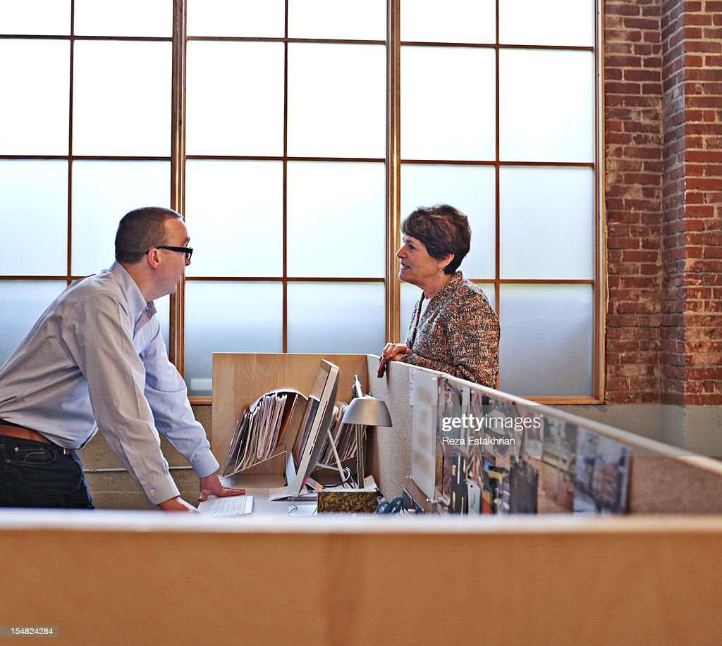 Business colleagues chat over office divide : Stock Photo