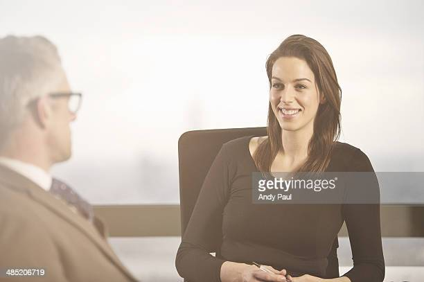 Business colleagues chatting at desk in office
