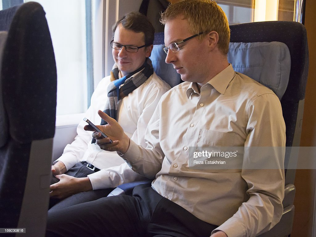 Business colleagues check cell phone : Stock Photo