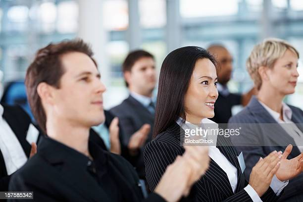 Business colleagues clapping hands during a meeting