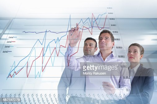 Business colleagues discussing graphs and charts seen on interactive display