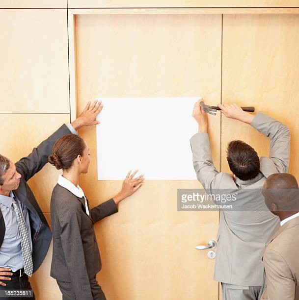 Business colleagues hammering billboard on wall