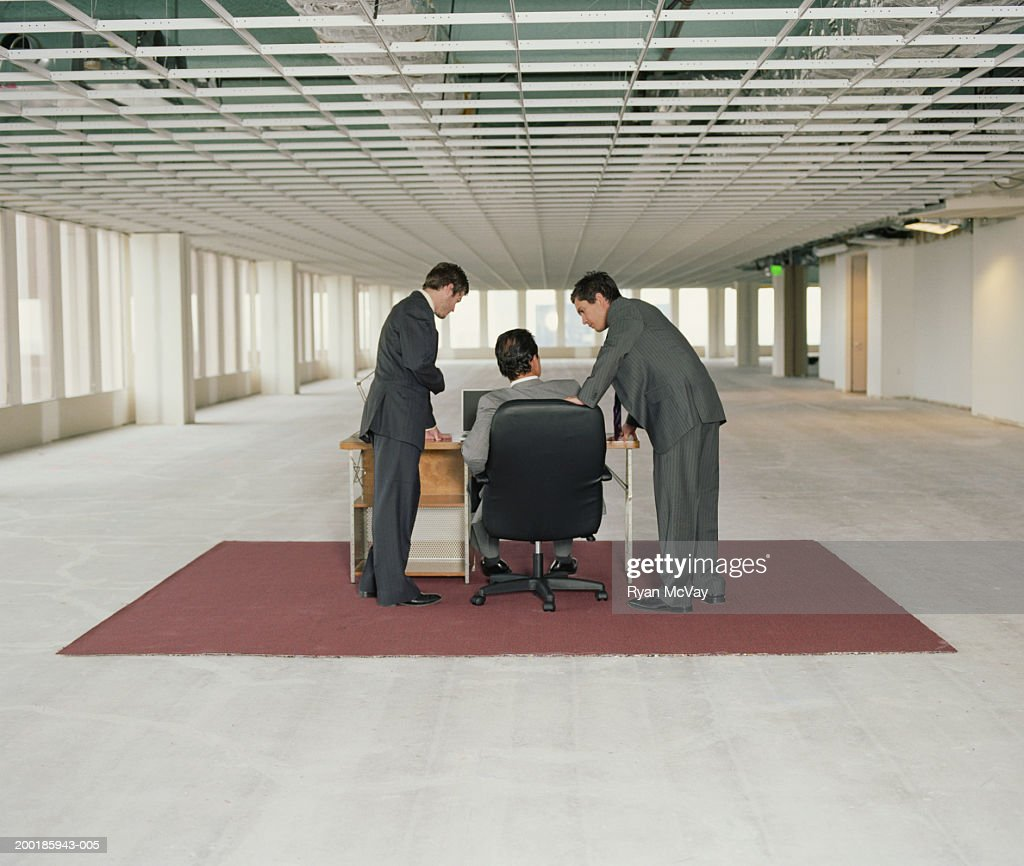 Business Colleagues Having Meeting At Desk Area In Empty