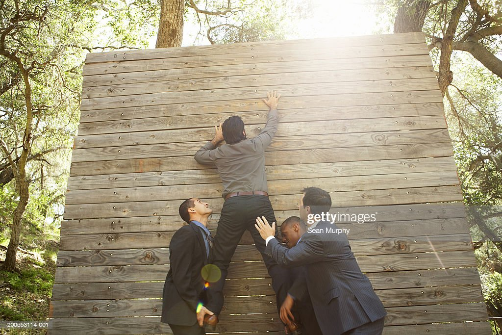 Business colleagues helping man go over obstacle wall