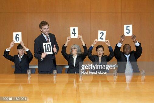 Business colleagues holding up cards with numbers, man standing