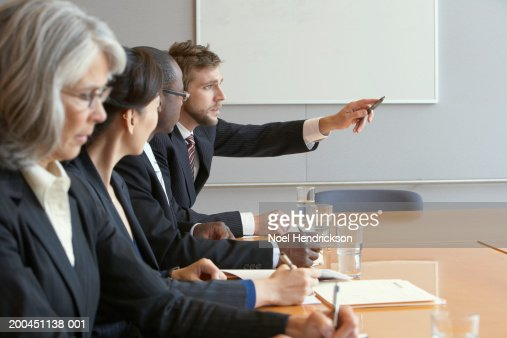 Business colleagues in meeting, man pointing : Stock Photo