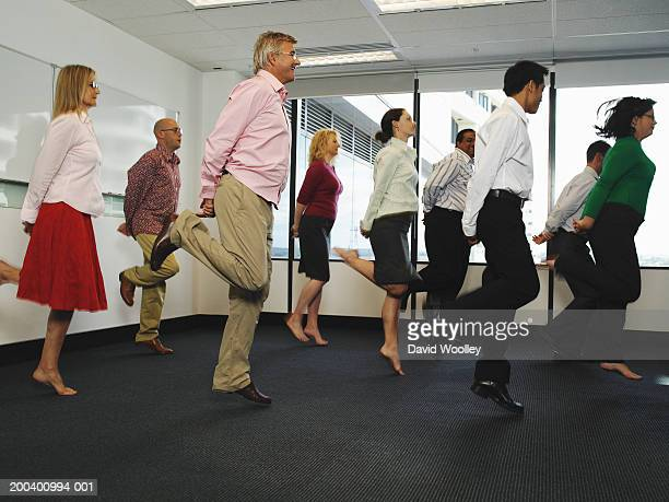Business colleagues jumping in office with hands behind backs