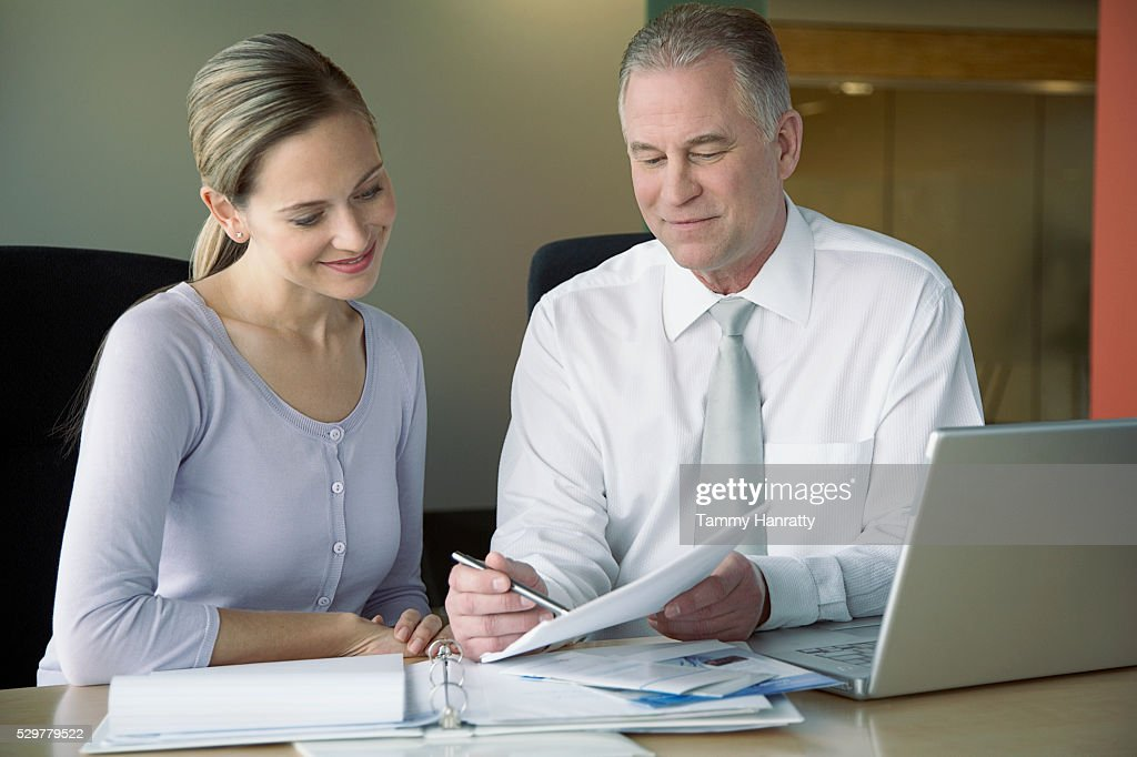 Business colleagues looking at documents : Photo