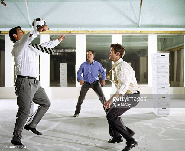 Business colleagues playing soccer in empty office building