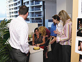 Business colleagues presenting woman with birthday cake at desk