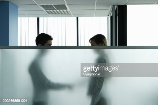 Business colleagues shaking hands behind screen in office