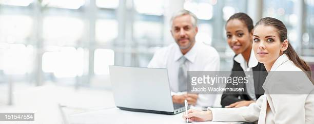 Business colleagues sitting at a table with laptop