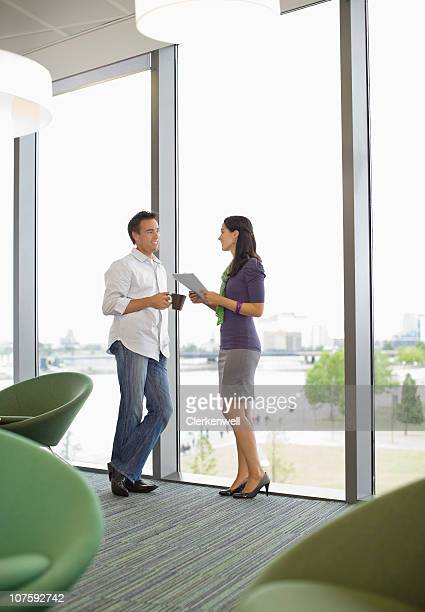 Business colleagues standing by bay window discussing on document in office canteen