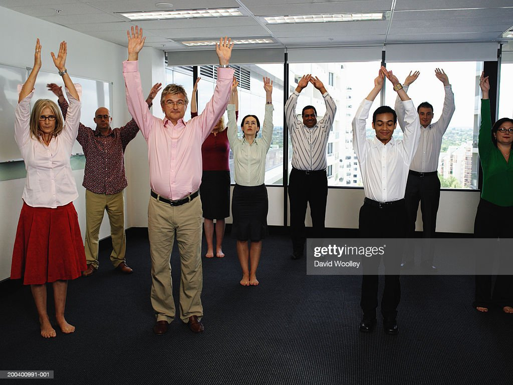 Business colleagues standing with arms raised in office