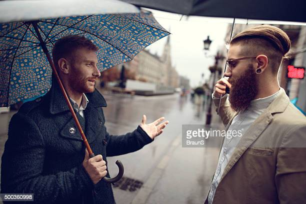 Business colleagues talking to each other on a rainy day.